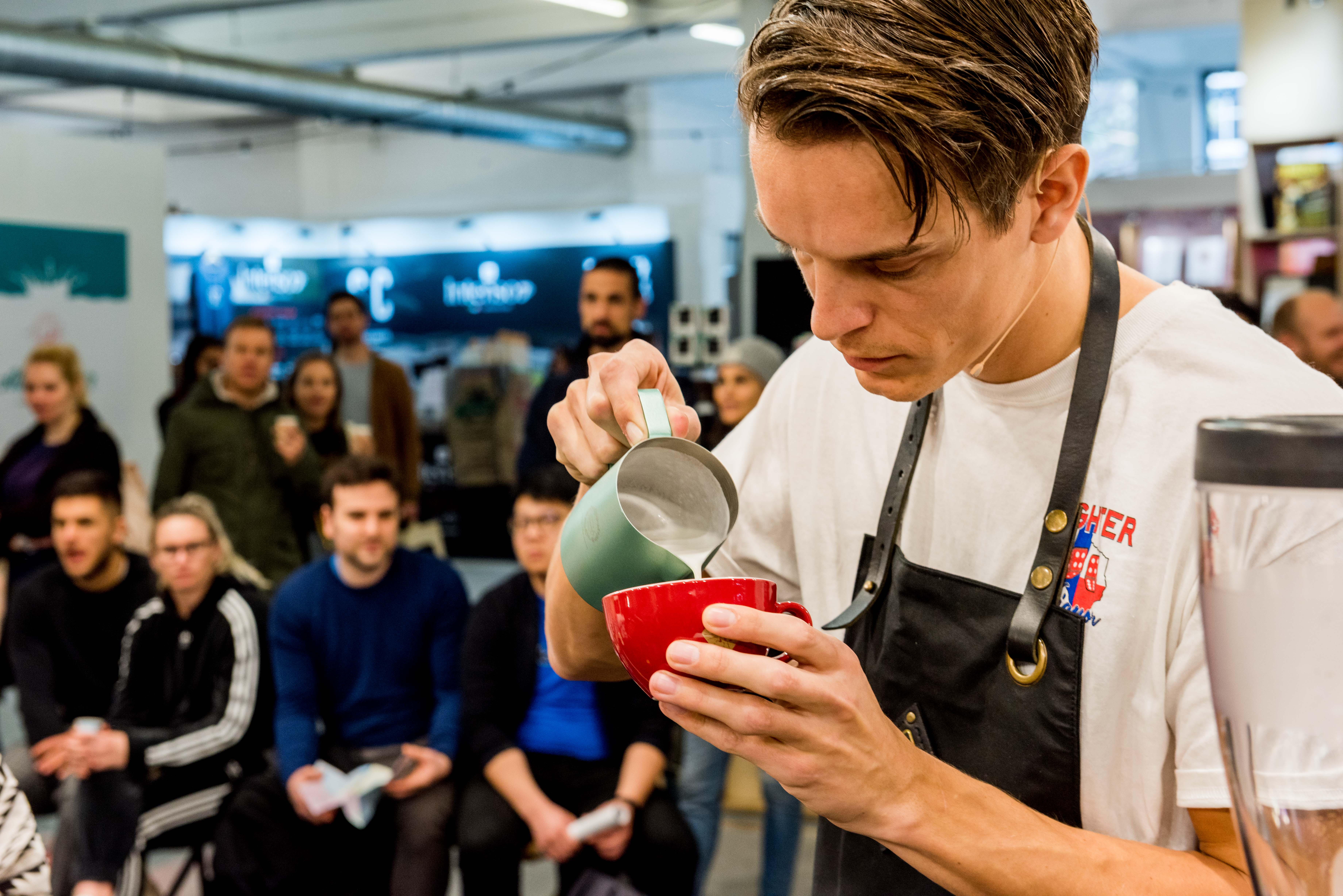 Rob Clarijs pours a latte into a red mug while onlookers watch.