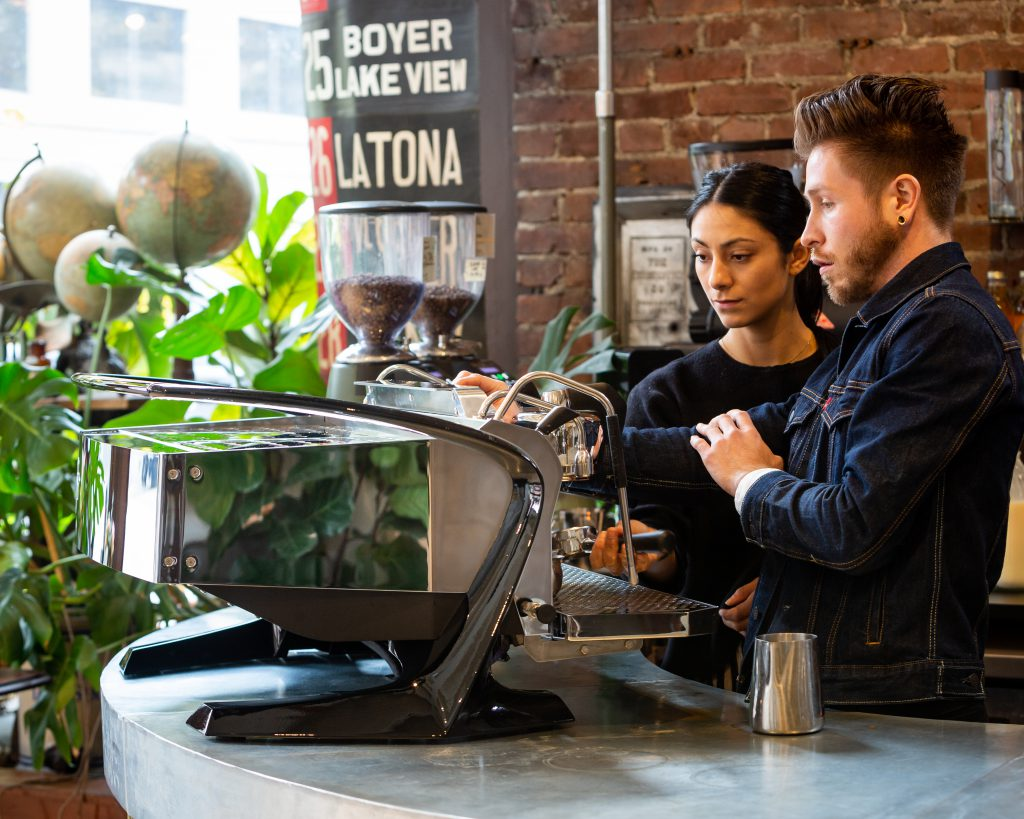 Two baristas making coffee on the Slayer Espresso Steam LP machine in a cafe.