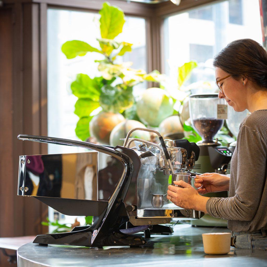 A barista making coffee on the Slayer Espresso Steam LP machine in a cafe.